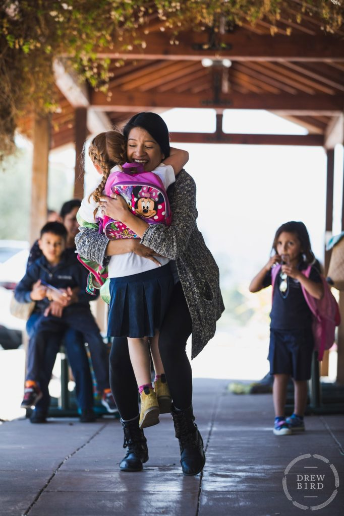 Mother hugs her daughter and picks her up at The Hillbrook School in Los Gatos, California. San Francisco education marketing photographer Drew Bird. San Jose school branding photographer.