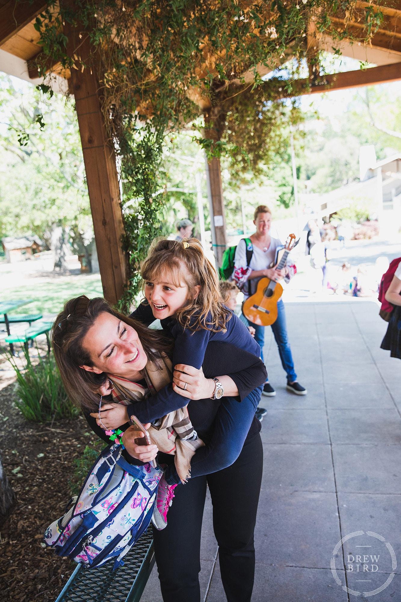 Mother gives her daughter a piggy back ride and picks her up at The Hillbrook School in Los Gatos, California. San Francisco education marketing photographer Drew Bird. San Jose school branding photographer.