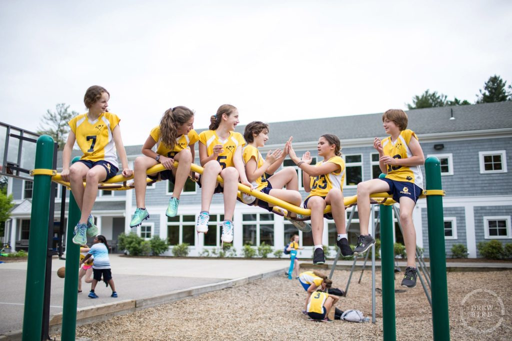 A group of girls in lacrosse uniforms sit on top of jungle gym on campus at the Charles River School in Boston. San Francisco education marketing photographer Drew Bird. San Jose school branding photographer.