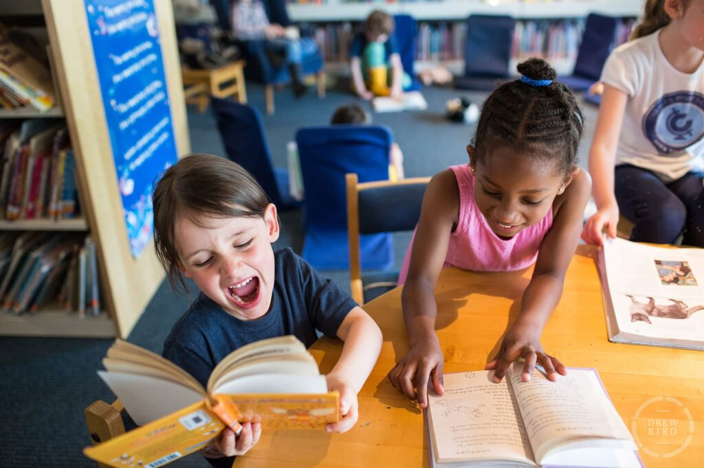Two girls reading a book and laughing at the Charles River School in Boston. San Francisco education marketing photographer Drew Bird. San Jose school branding photographer.