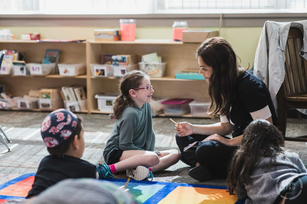 A teacher works with a young student in the classroom at solomon schechter day school in Boston. San Francisco education marketing photographer Drew Bird. San Jose school branding photographer.