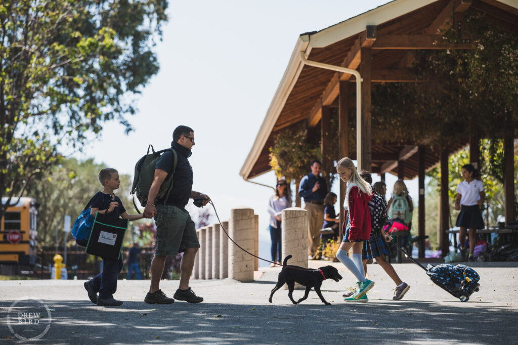 Students and parents arrive for the school day and walk across campus with their puppy dog on a leash. Hillbrook School. San Jose education brand photography and independent school photographer Drew Bird.