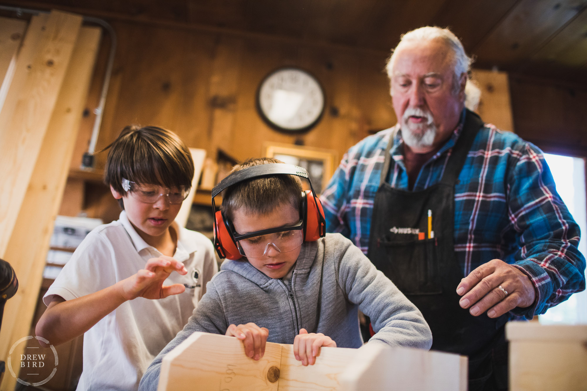A man teacher helps two grade school students in shop class at the Hillbrook School in Los Gatos, California. San Francisco education brand photography and San Jose independent school photographer Drew Bird.