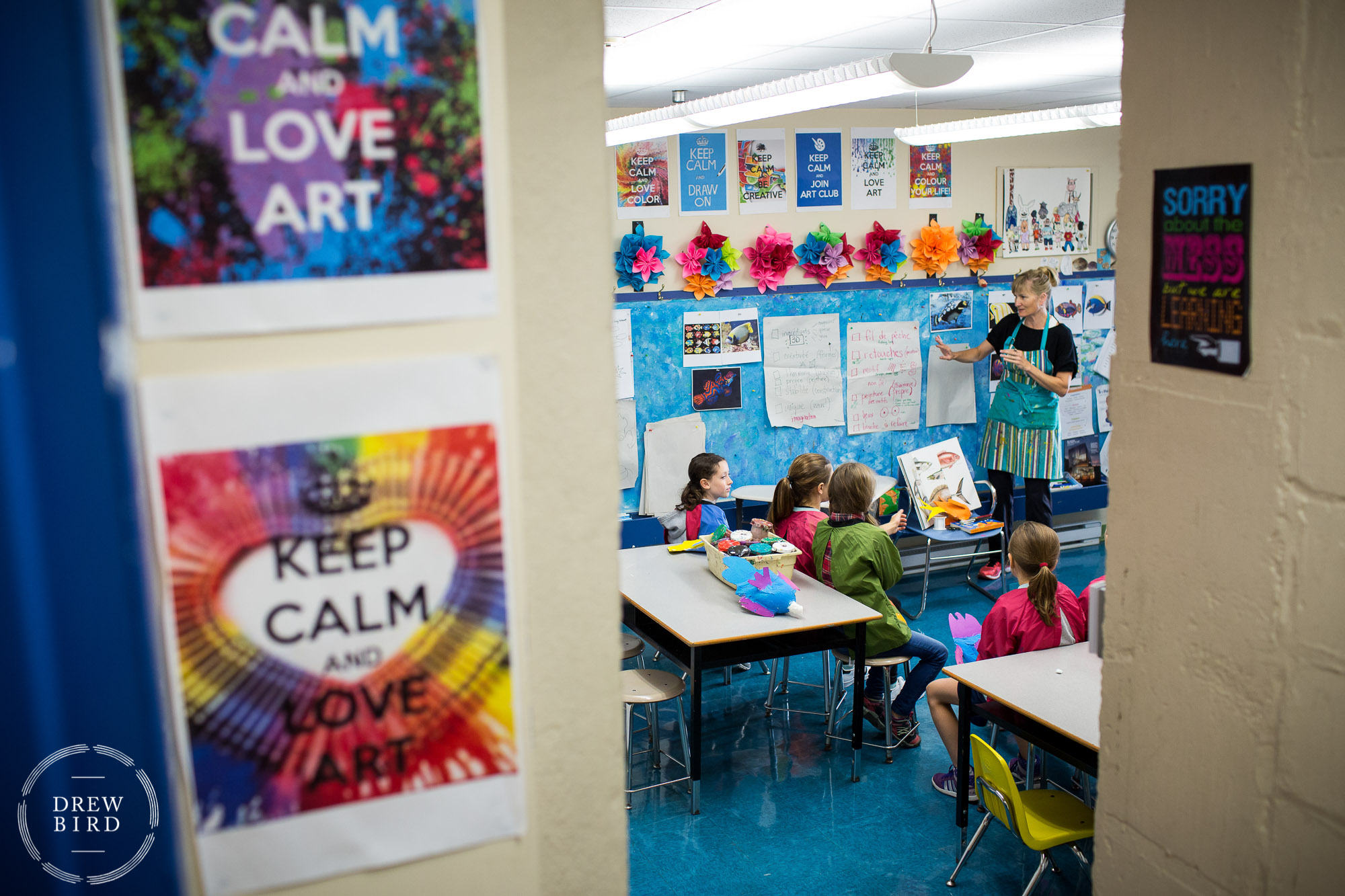 A primary school woman teacher with her class and signs that read keep calm and love art at St. George's School of Montreal in Quebec, Canada. San Francisco independent school photographer and private school marketing photography and brand lifestyle photography by Drew Bird.