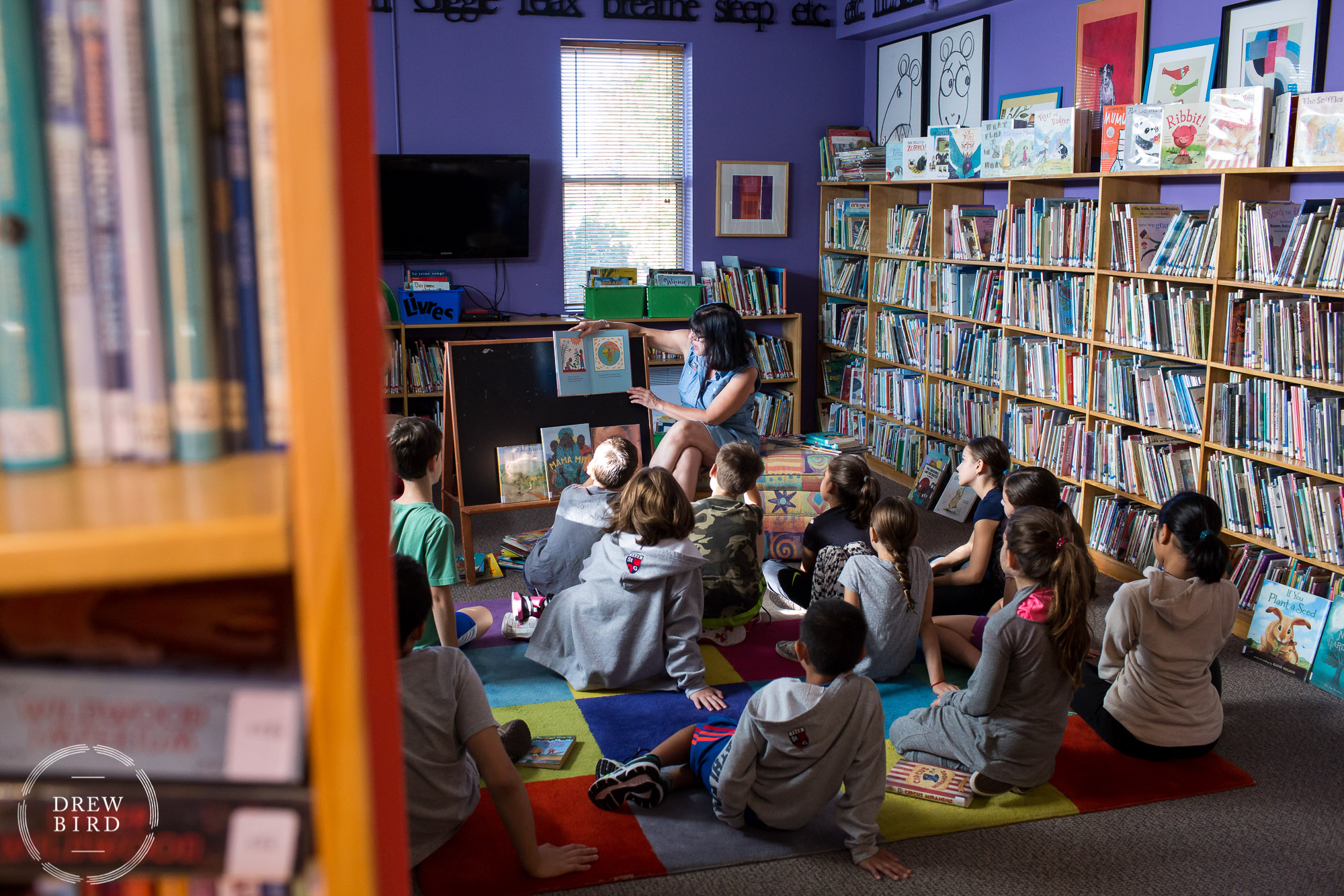 A woman teacher reads a book to a group of primary school students sitting on the floor in library at St. George's School of Montreal in Quebec, Canada. San Francisco independent school photographer and private school marketing photography and brand lifestyle photography by Drew Bird.