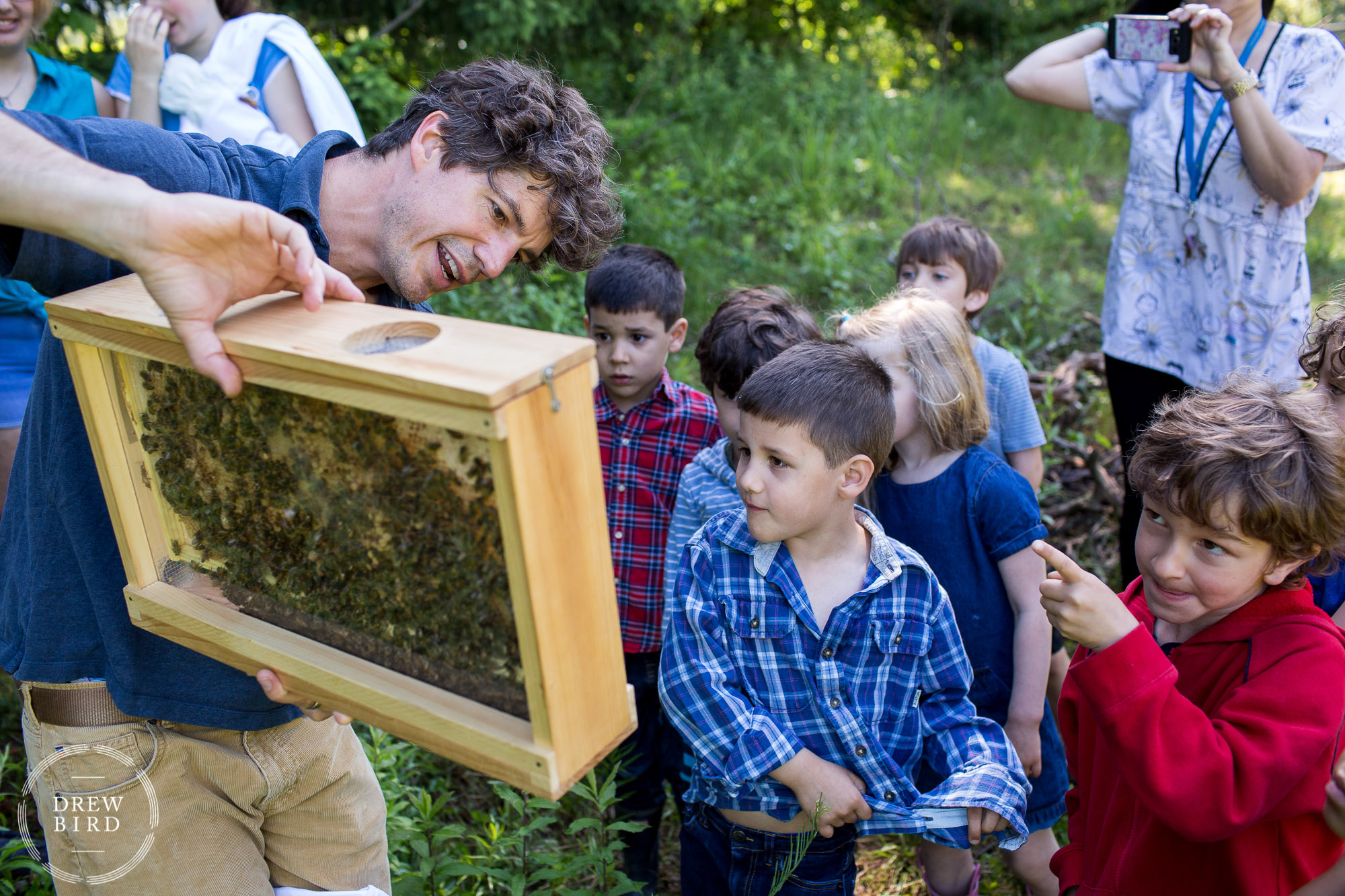 A man teacher shows a group of grade school students a bee hive during an outdoor class at Poughkeepsie Day School in New York. San Francisco independent school photographer and private school education lifestyle photography by Drew Bird.